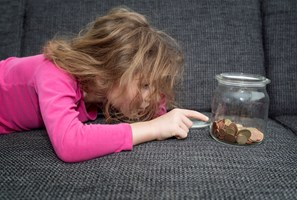 Child lying down on sofa counts coins in glass jar