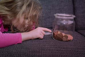 Young child lying on sofa counting coins in a glass jar