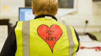 Worker sitting facing computer wearing yellow hi vis jacket with 'safety at heart' written on back