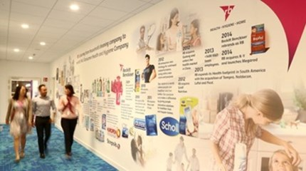 Three RB employees walking along a corridor with the RB timeline on the wall