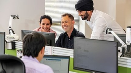 Man with black turban stands next to two colleagues looking at computer screen