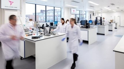 Scientists wearing white lab-coats walk around an RB laboratory