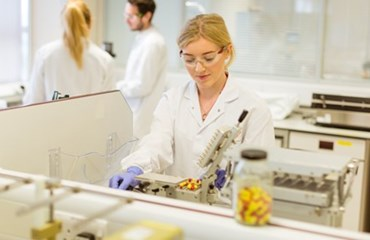 Blonde scientist in lab looks down intently at microscope
