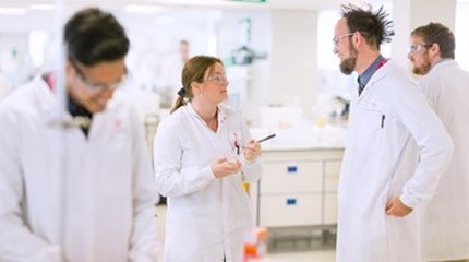 Four scientists wearing protective goggles and white lab-coats working in a Scholl lab