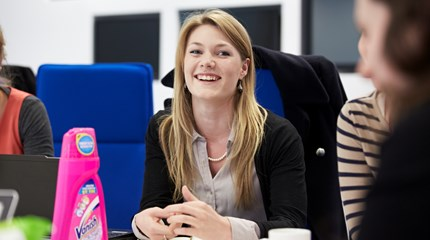 Smiling woman sits at meeting room table with Vanish bottle in front of her