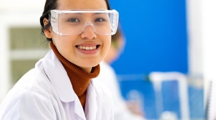 Scientist in a lab wearing protective goggles and white lab-coat