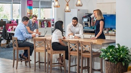 Colleagues sitting and standing around a table in an office kitchen