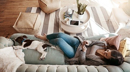 Dog and owner lying on a sofa in a living room