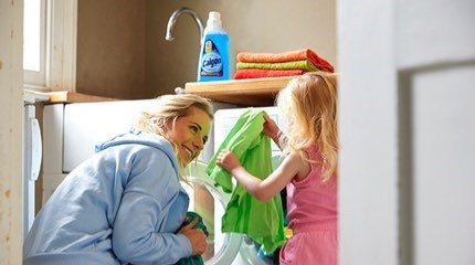Parent in blue jumper kneels next to child holding green t shirt from open washing machine