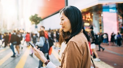 Busy street crossing person with beige jacket looks at their phone