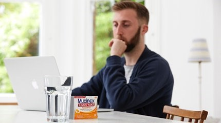 Man with pensive expression sitting at table looking at MacBook with glass of water and box of Mucinex tablets