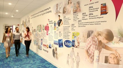 Three RB colleagues walk down office corridor with RB timeline on wall