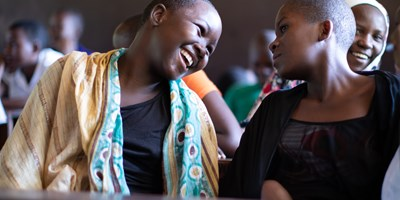In a classroom a young person tells a joke to their friend while girl in headscarf smiles behind them