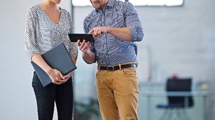 Two people stand together in room looking at a tablet device