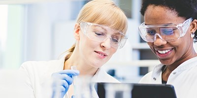 Two scientists wearing protective goggles working together in a lab