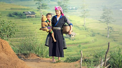 Female farm worker carries child while working in field