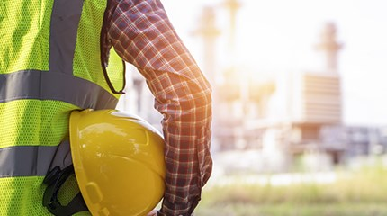 Worker looking at factory wearing hi vis jacket and holding yellow protective helmet