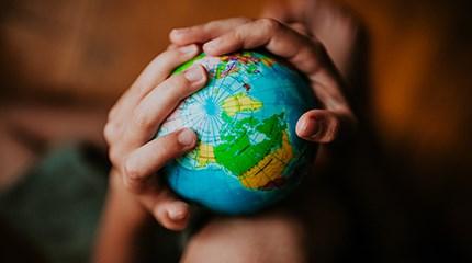 Children's hands holding toy globe