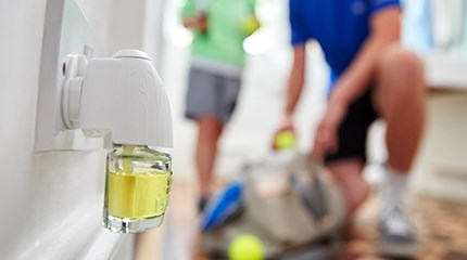 AirWick device plugged into family home corridor while child and parent pack tennis bag