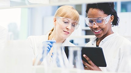 Two RB scientists wearing white lab coats look at a tablet while working in a laboratory