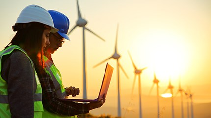Two wind farm workers stand looking at laptop in front of wind turbines