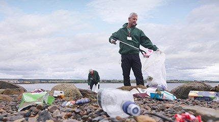 Two volunteers picking up plastic waste on a beach