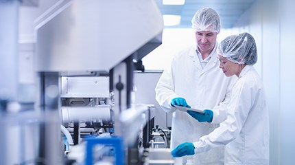 Two laboratory workers looking at a tablet device while in a lab