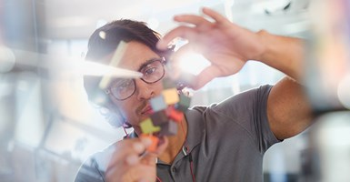 Scientist wearing glasses holds up coloured cubes to analyse them with light shining from behind